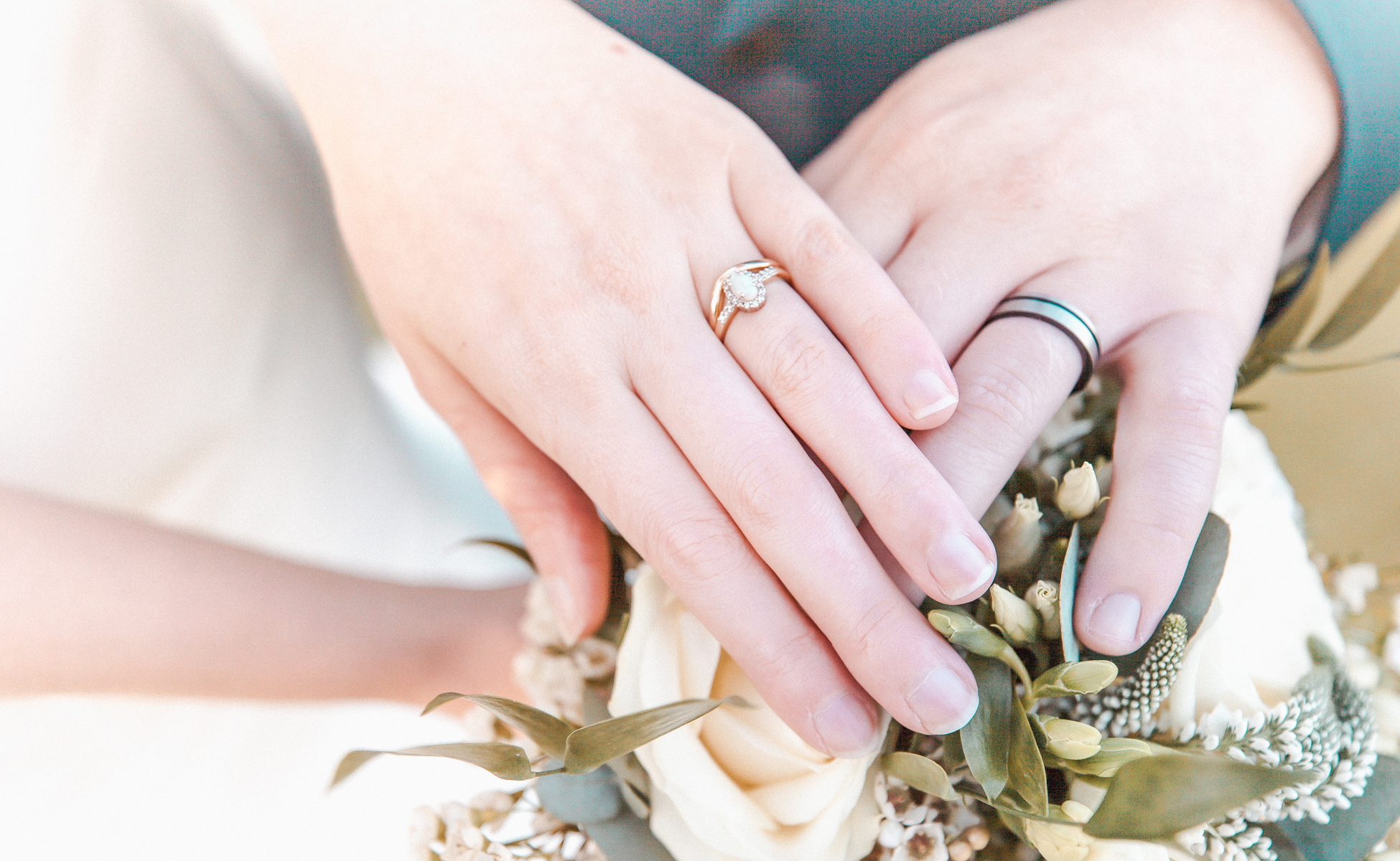 Married couple hold hands and display wedding rings