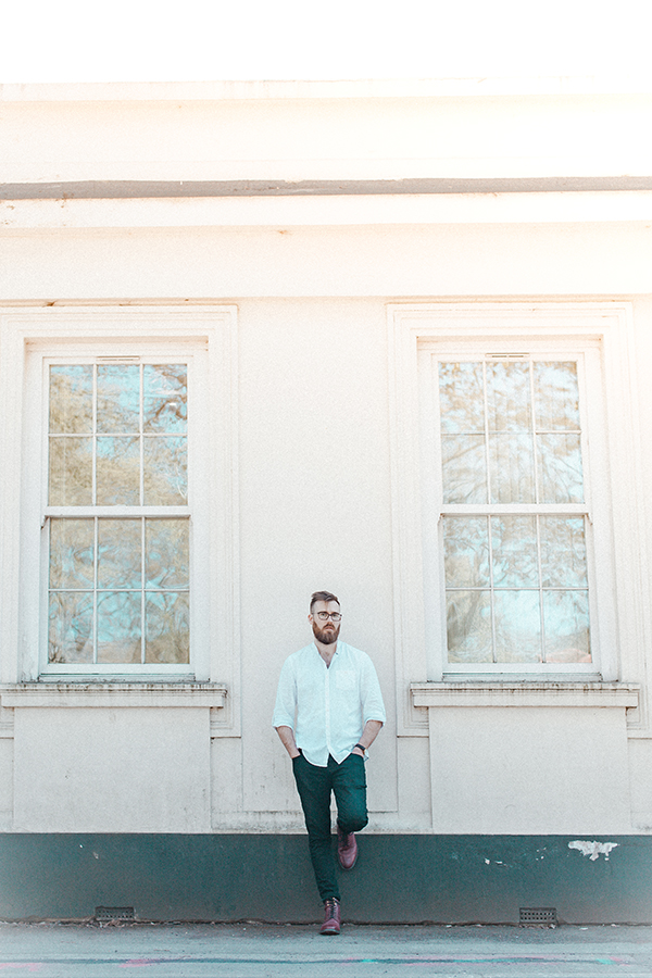 Portrait of man in front of pink building by Hanne Brooks Photography