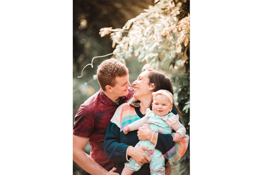 Family smiling and holding baby by Hanne Brooks Photography